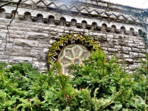 A window on the side of the chapel, peeking out from behind some shrubbery, a screen protecting it from wayward stones.